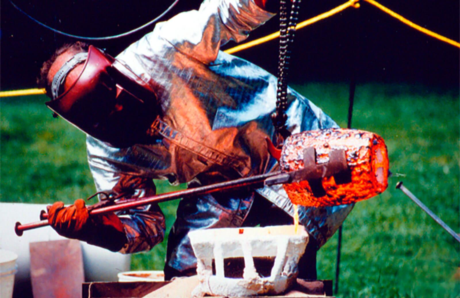Sculptor Andrew DeVries pouring molten bronze