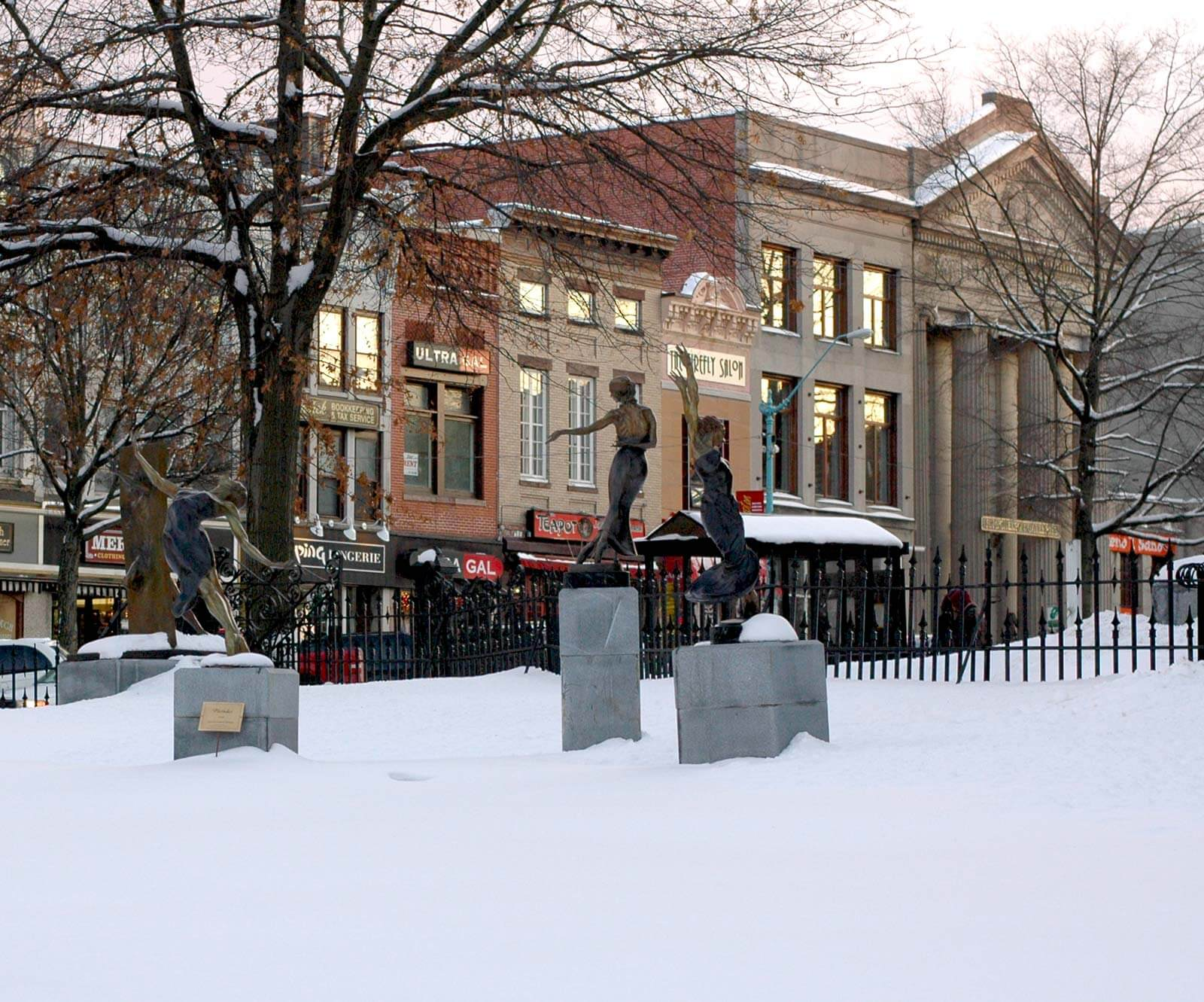 Three bronze dance sculptures by Andrew deVries in the winter Northampton, MA