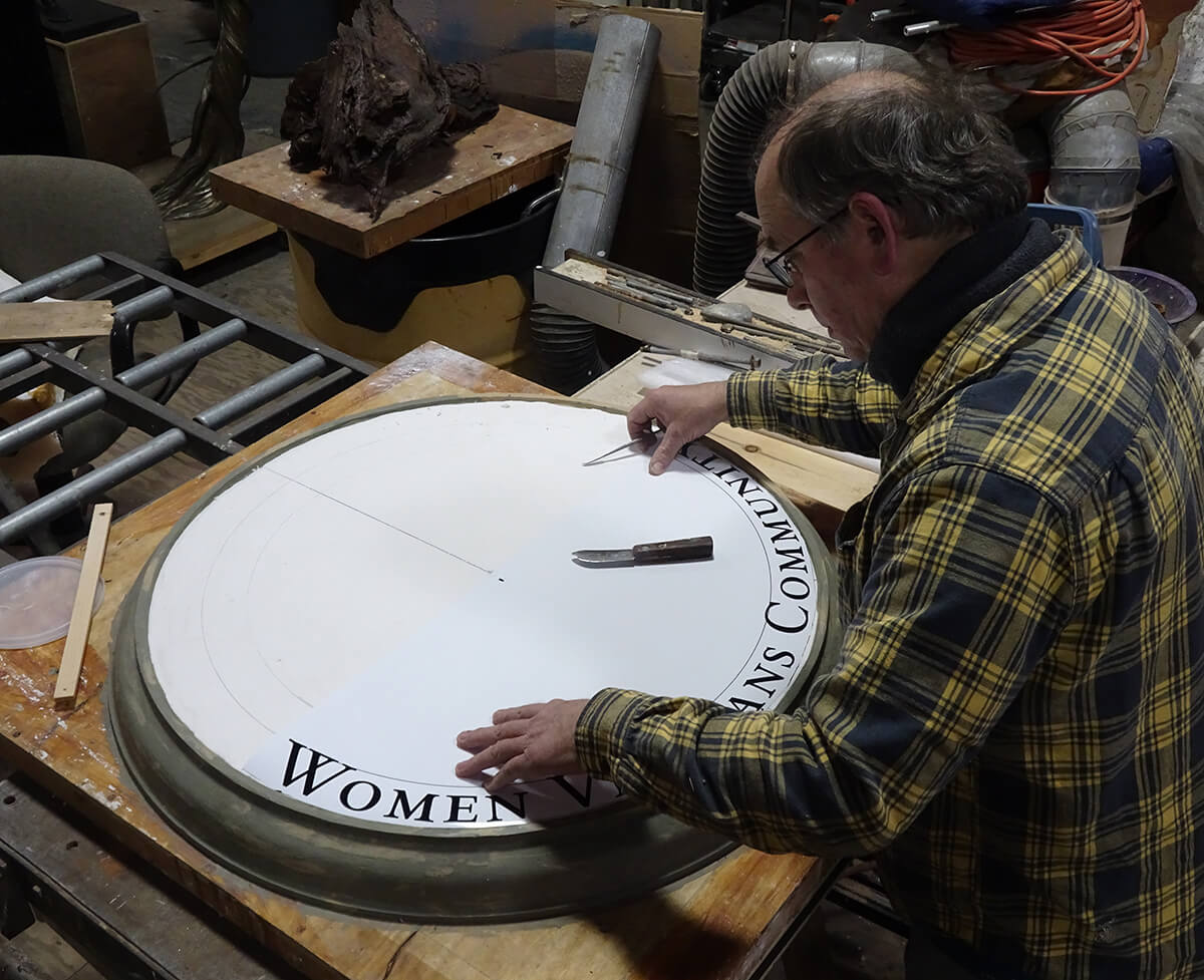 Sculptor Andrew DeVries works on the lettering for a roundel of Catherine A. Doherty
