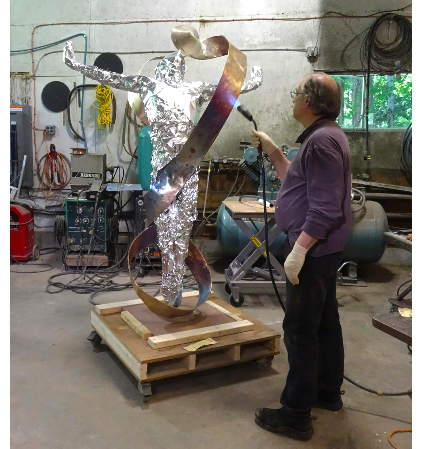 Sculptor Andrew DeVries heats the Mobius strip in preperation for the patina.