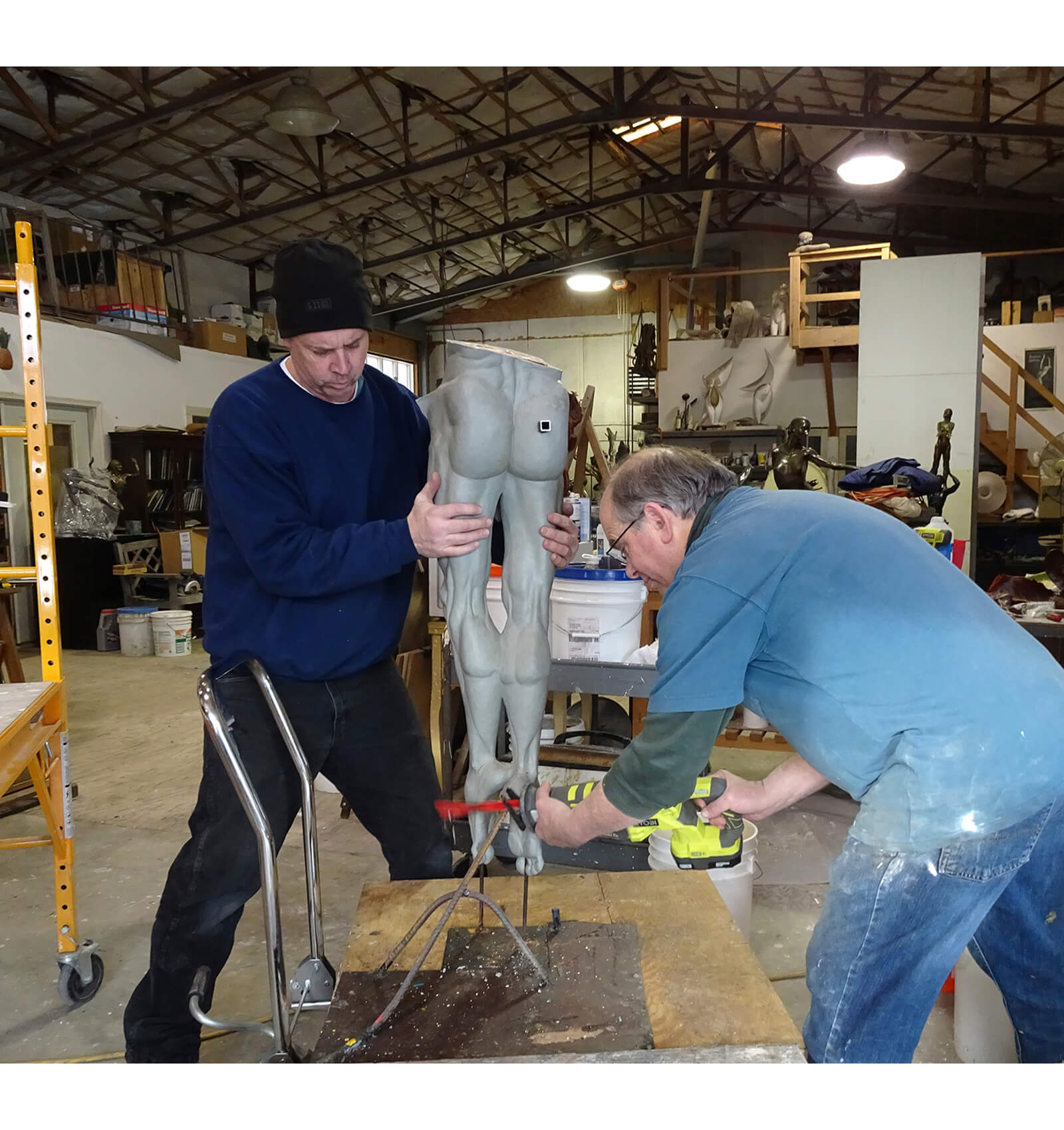 Sculptor Andrew DeVries and assistant Bill Carey cut the large clay of Echoes to ready it for the rubber mold.
