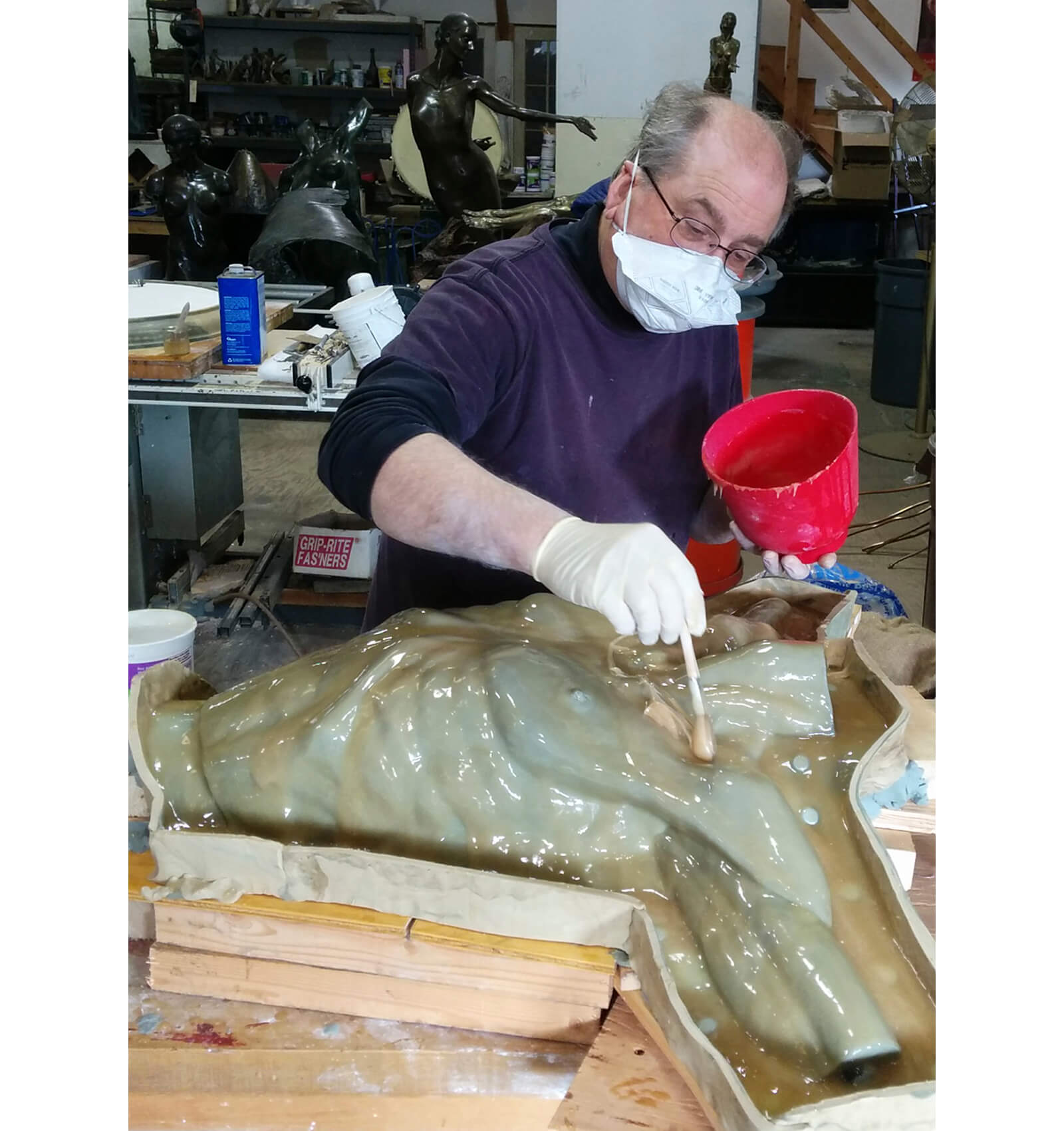 Andrew DeVries paintint rubber mold material on the upper torso of Echoes