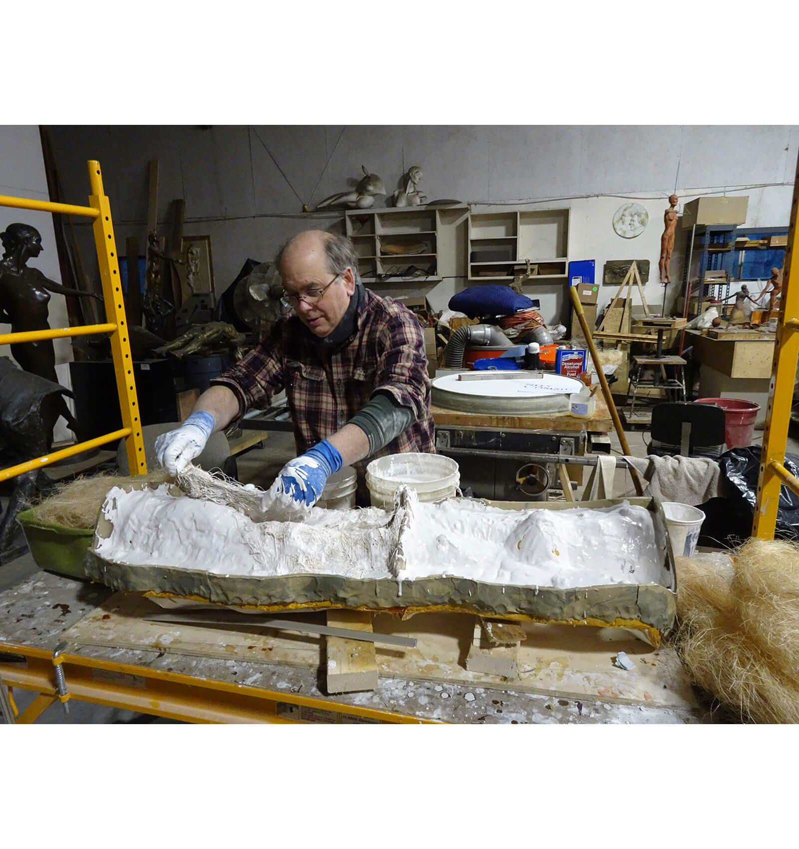 Sculptor andrew deVries applyin plaster back up mold over the rubber mold.