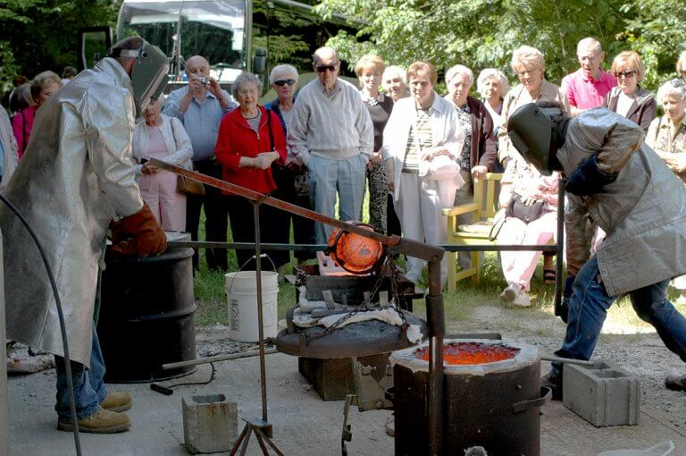 An group art  tour watches the pouring of bronze at DeVries Fine Art International.