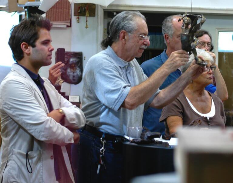 A collector examines one of andrew's bronze sculptures during a lecture at DeVries Fine Art gallery