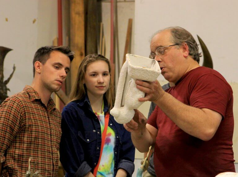 Two young visitors in rapt attention as sculptor andrew DeVries explains one of the steps in the lost wax proceaa at DeVries fine Art International.